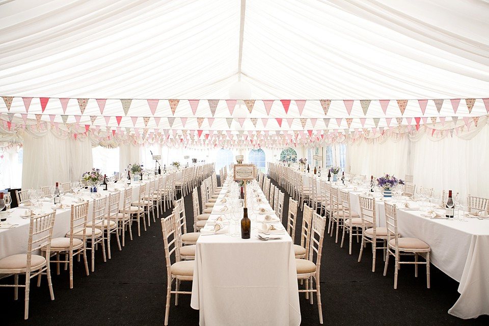 Bridebook.co.uk- wedding marquee with rectangle tables decorated with pink bunting