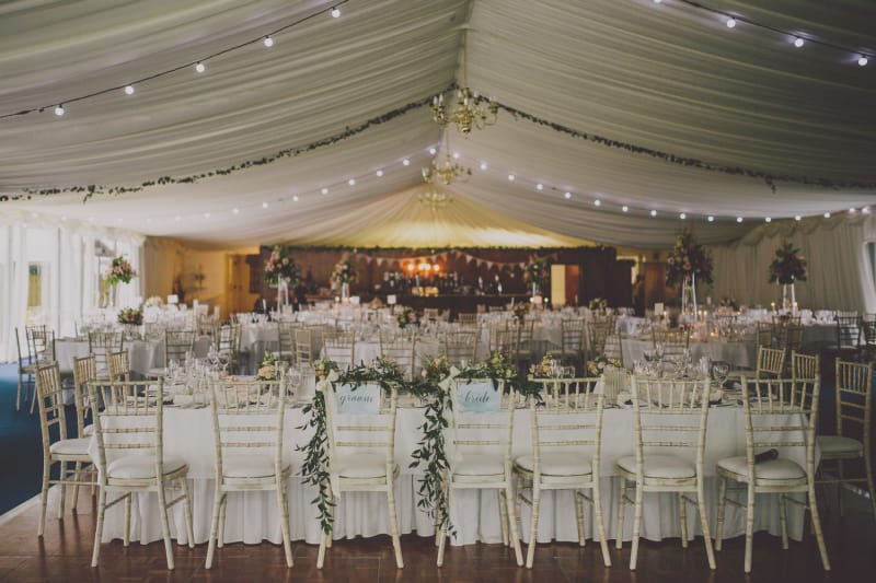 Bridebook.co.uk- wedding marquee with bride and groom chairs at the forefront