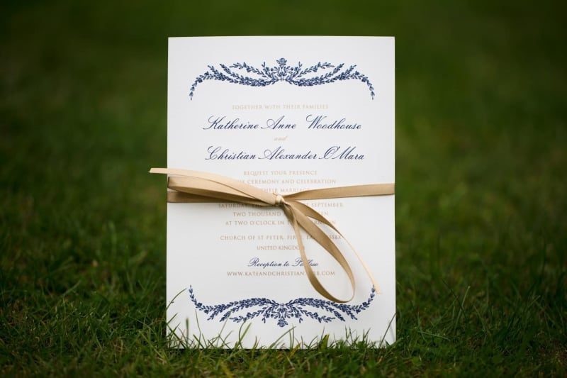 Bridebook.co.uk- wedding invitation sitting on grass tied with yellow ribbon
