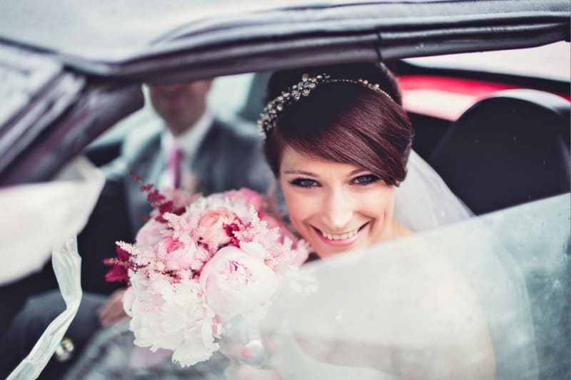 Bridebook.co.uk- bride smiling from the wedding car