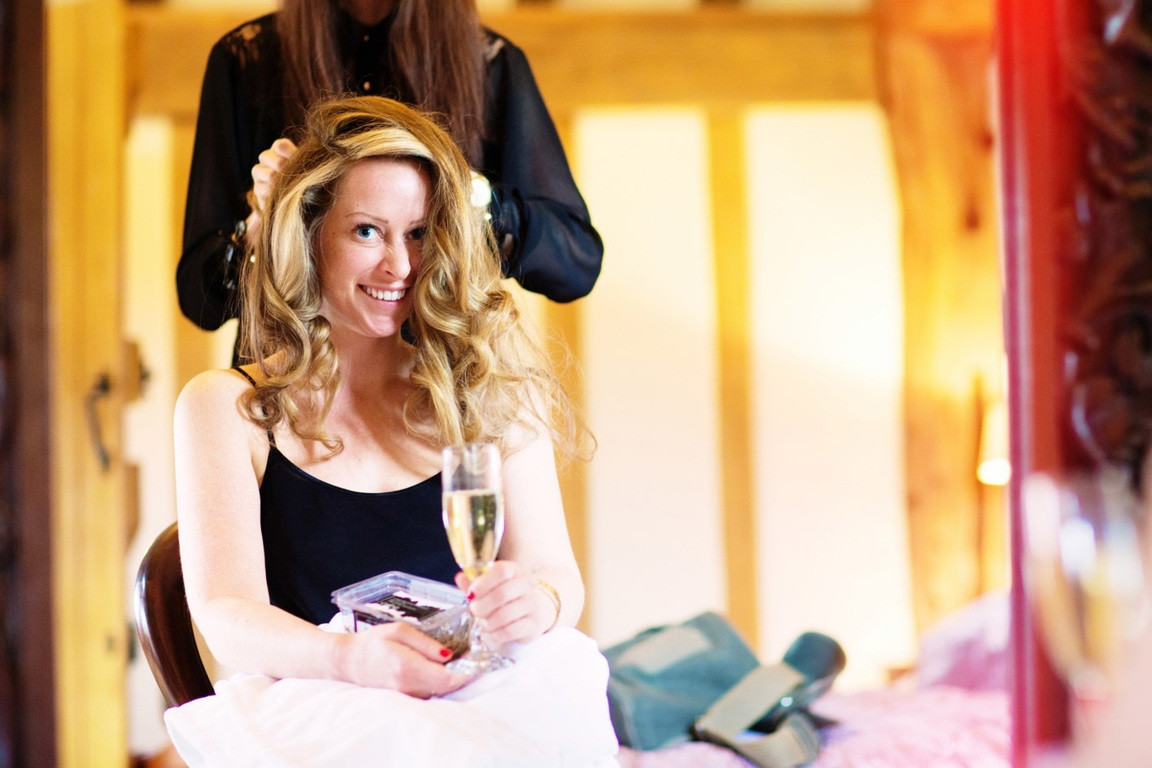 Bridebook.co.uk- bride with a glass of champagne having her hair styled