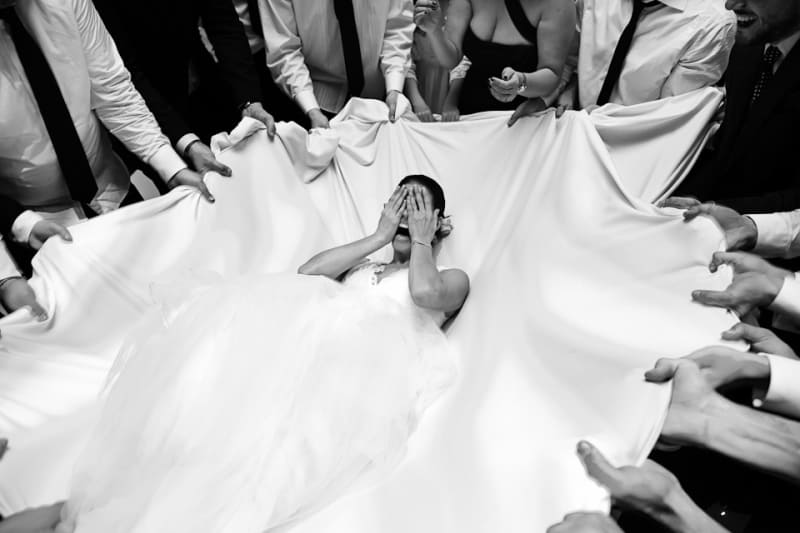 Bridebook.co.uk- bride falling backwards onto white sheet held by guests