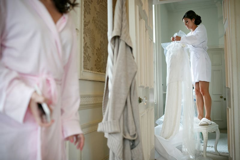Bridebook.co.uk- bride taking her wedding dress off the hanger