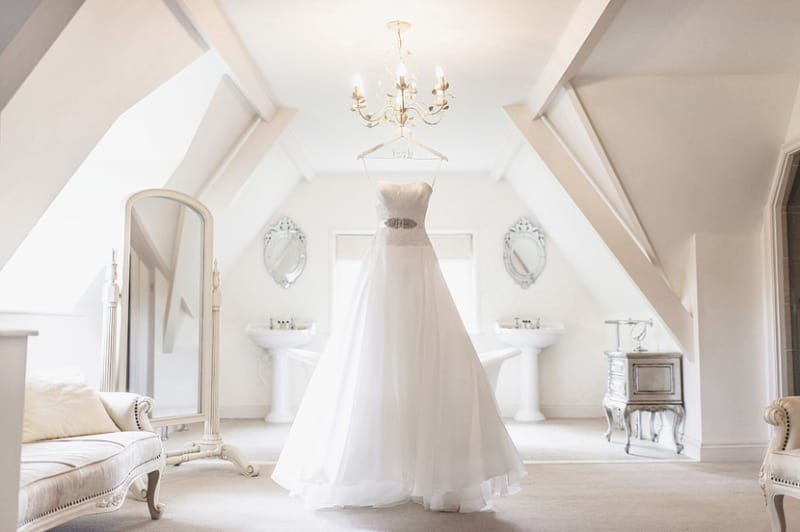 Bridebook.co.uk- white wedding dress hanging up in bridal suite