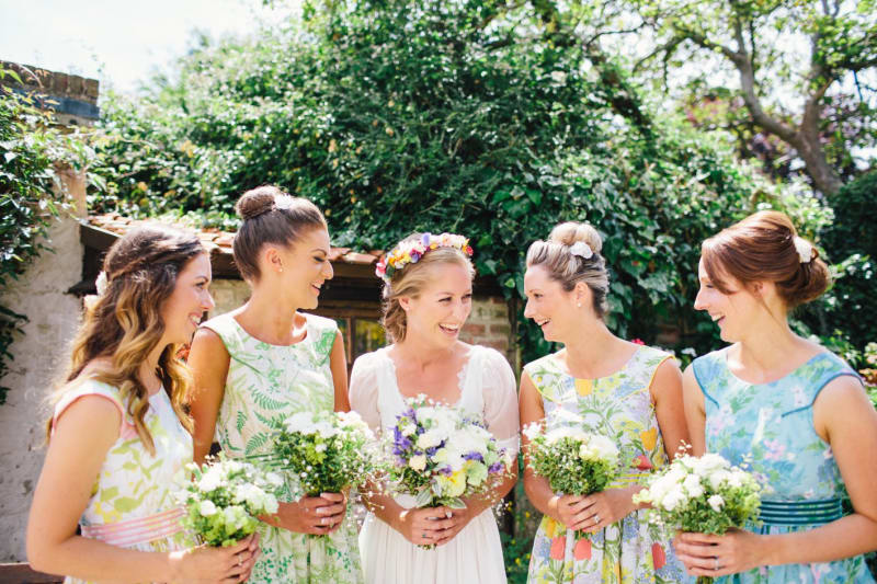 Bridebook.co.uk- bride and bridesmaids holding bouquets and smiling
