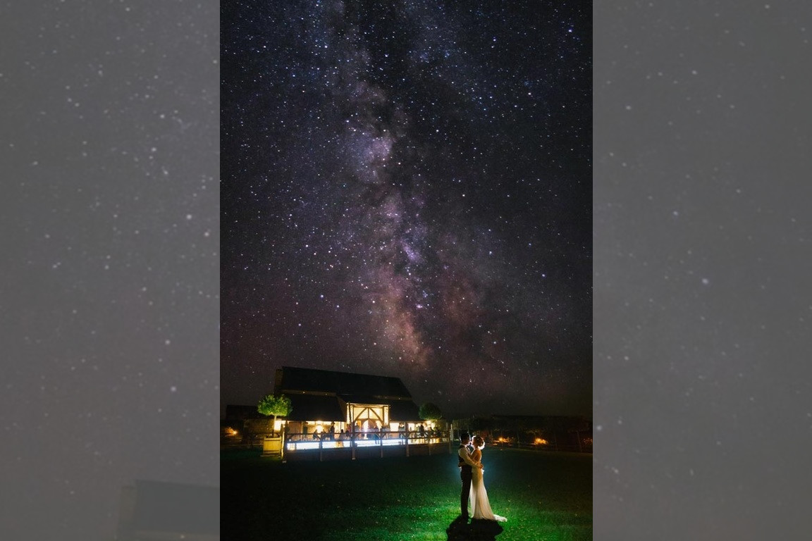 Bridebook.co.uk- bride and groom in front of the venue and starry sky