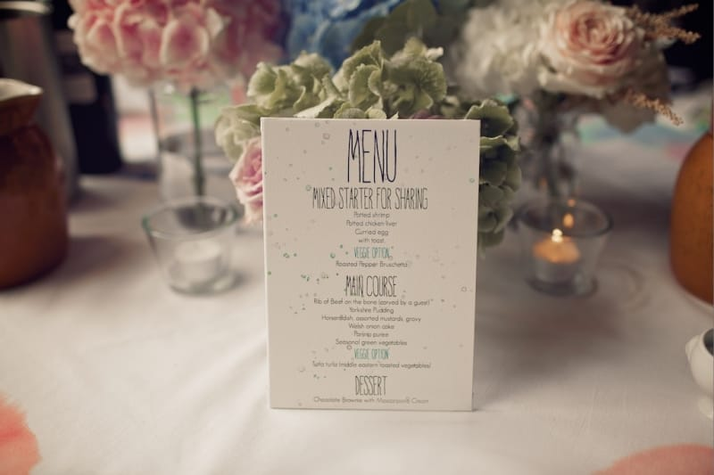 Bridebook.co.uk- Wedding menu propped up on some flowers