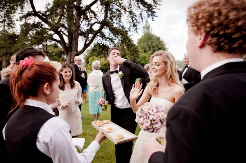 Bridebook.co.uk- bride and groom having canapes