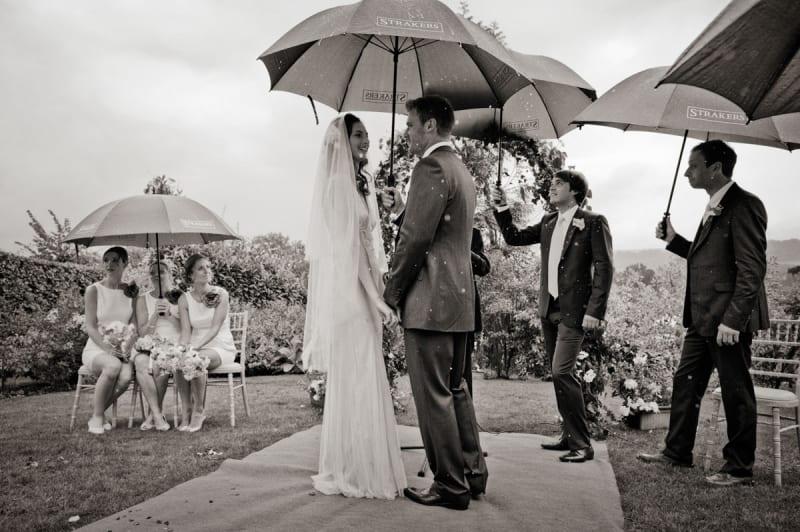Bridebook.co.uk- bride and groom in outdoor ceremony under umbrellas