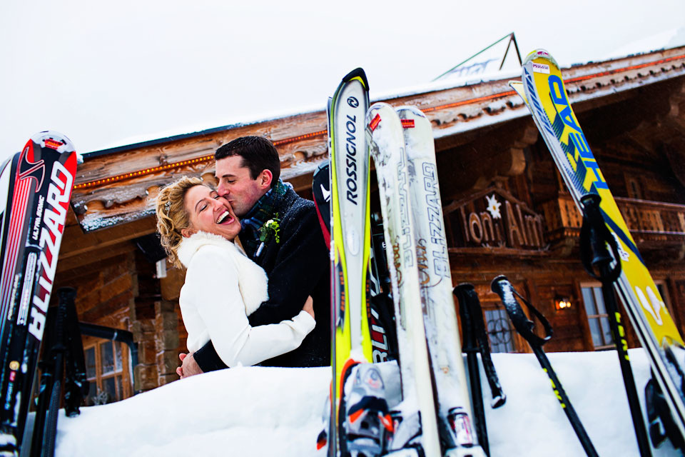 Bridebook.co.uk- bride and groom kissing in front of skiis