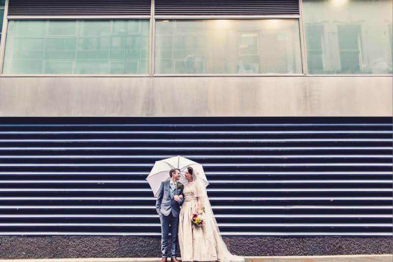 Bridebook.co.uk- bride and groom standing under white umbrella