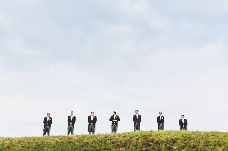 Bridebook.co.uk- groom and ushers standing on a hill against the sky