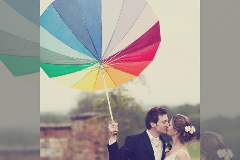 Bridebook.co.uk- bride and groom kissing under multicoloured umbrella