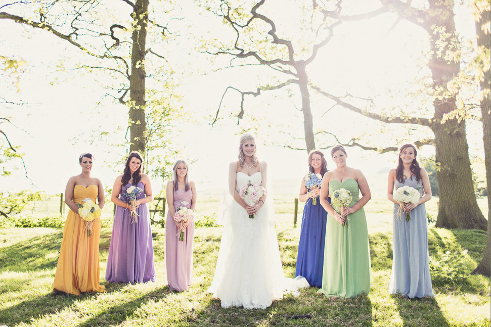 Bridebook.co.uk- bride and bridesmaids in differently coloured dresses holding bouquets