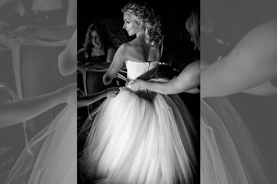 Bridebook.co.uk- bride getting laced into her dress