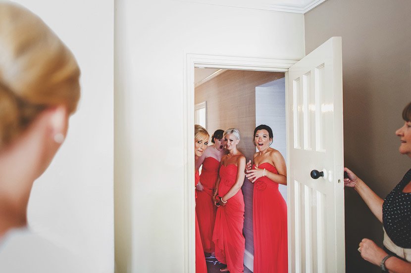 Bridebook.co.uk- bridesmaids dressed in red see the bride for the first time