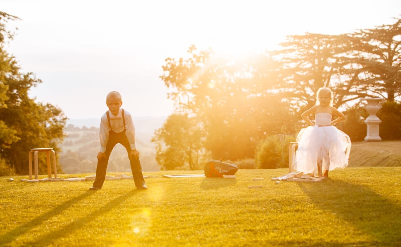 Bridebook.co.uk- flower girl and ring bearer playing in the sun