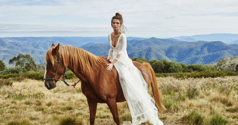 Bridebook.co.uk bride in wedding dress and bridal hair on horse