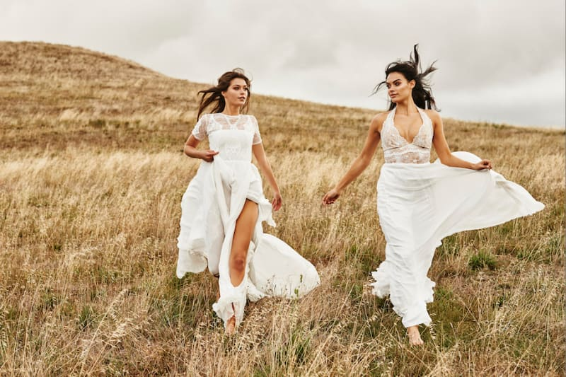 Bridebook.co.uk two brides in wedding dresses running in field