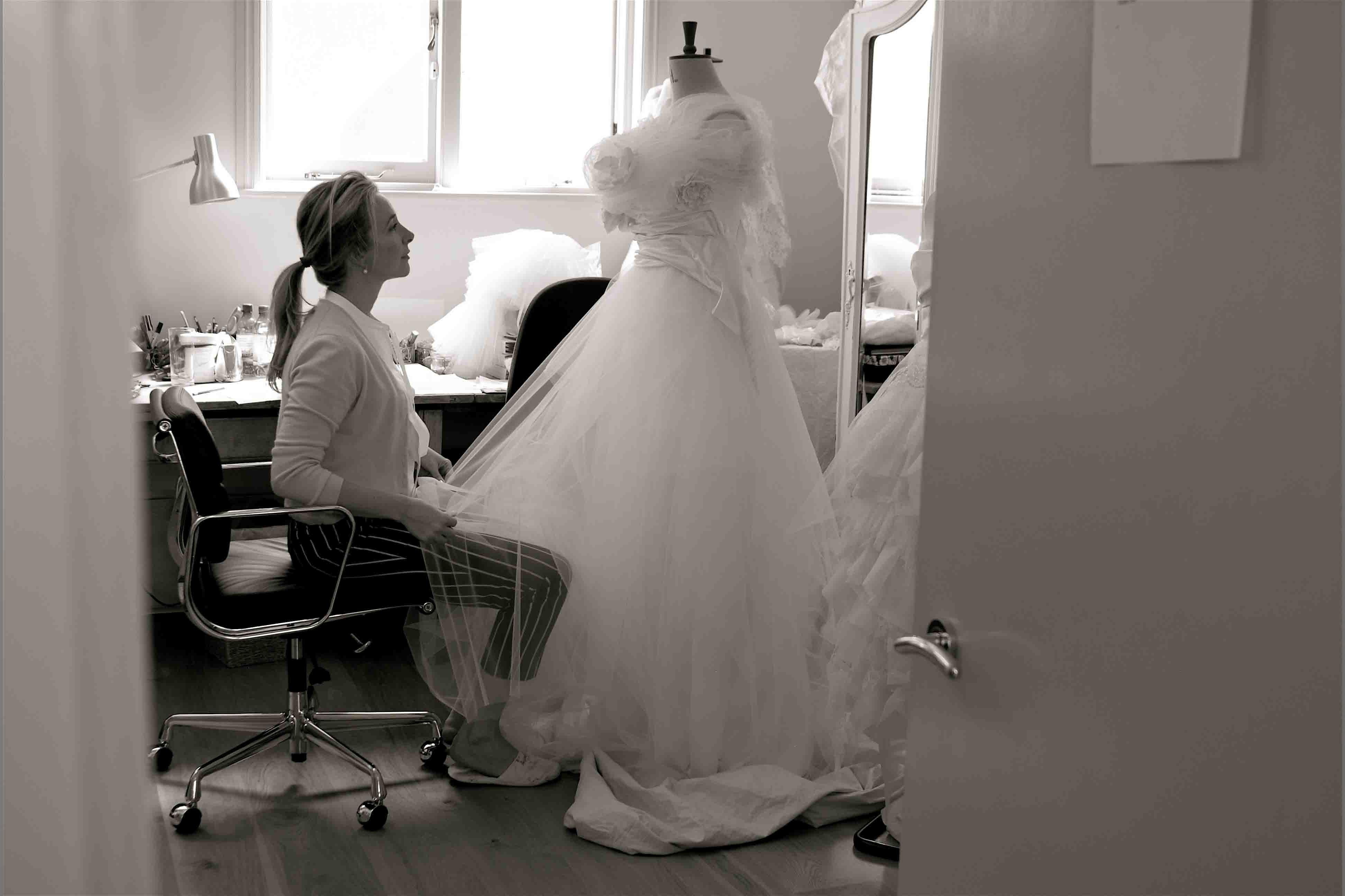 bridebook.co.uk phillipa lepley at work on a dress in her studio