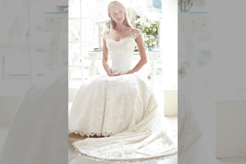 bridebook.co.uk-phillipa-lepley dress on model sitting with hands in lap
