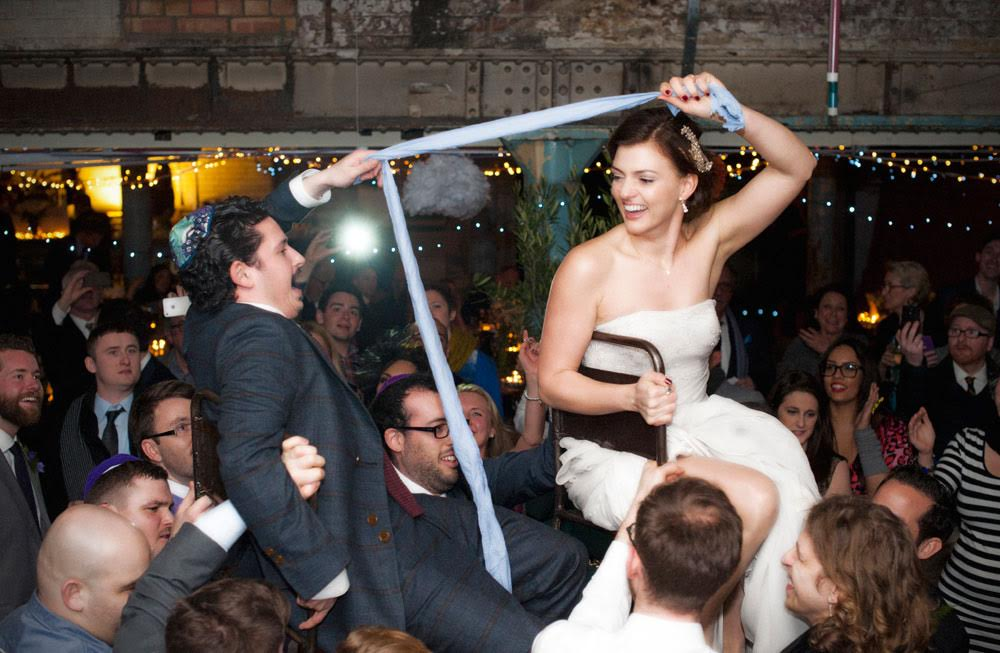 bridebook.co.uk-smashing-the-glass couple being lifted up on a chair holding a blue cloth between them