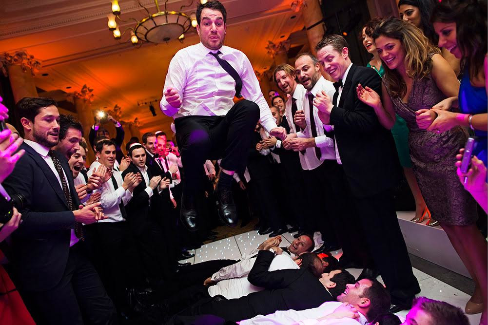 bridebook.co.uk-smashing-the-glass-groom jumping over wedding guests