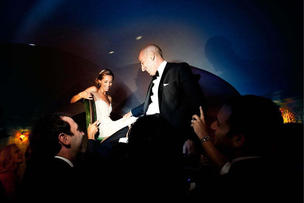 bridebook.co.uk-smashing-the-glass- couple on chairs being lifted up