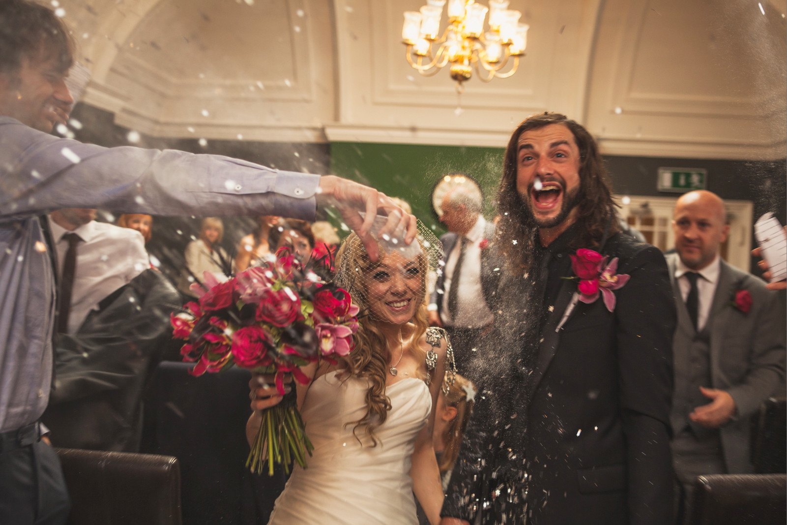 bridebook.co.uk happy couple being showered in confetti