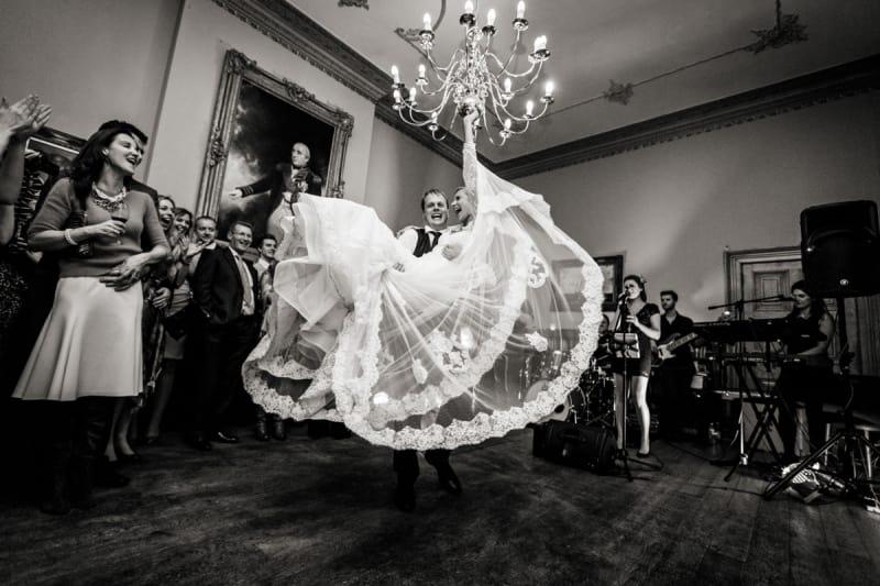 Bridebook.co.uk- groom lifting bride as guests applaud
