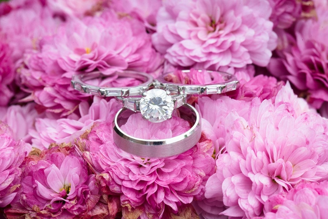 Bridebook.co.uk- wedding rings and engagement ring on top of pink flowers