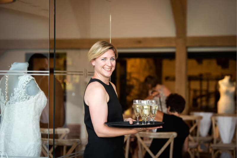 Woman in black dress holding tray with glasses of champagne and smiling at the camera.