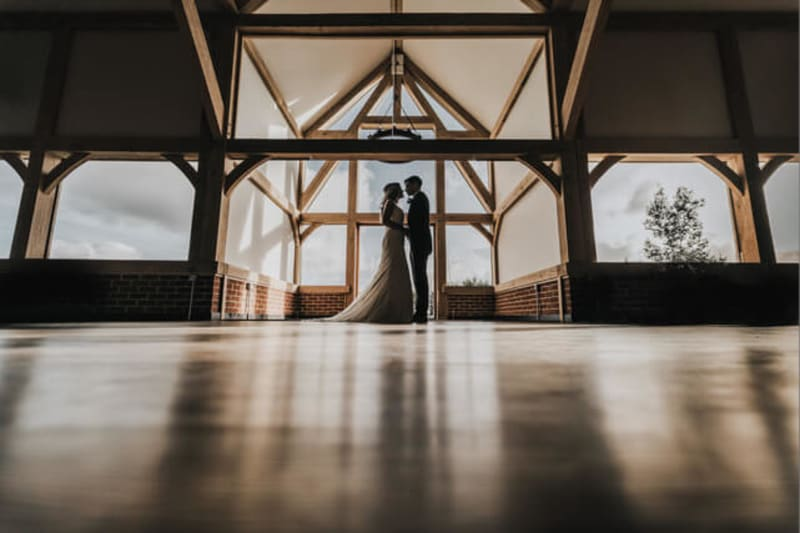 Silhouette of a bride and groom standing under barn beams.
