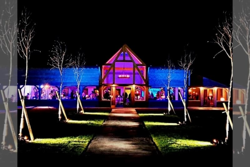 Barn venue lit up at night.