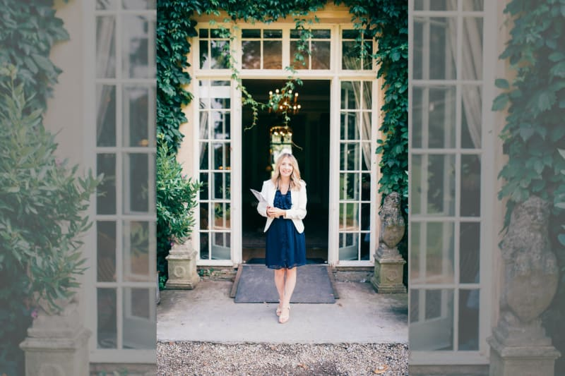 Smartly dressed woman standing in front of tall glass doors with a clipboard and smiling at camera.