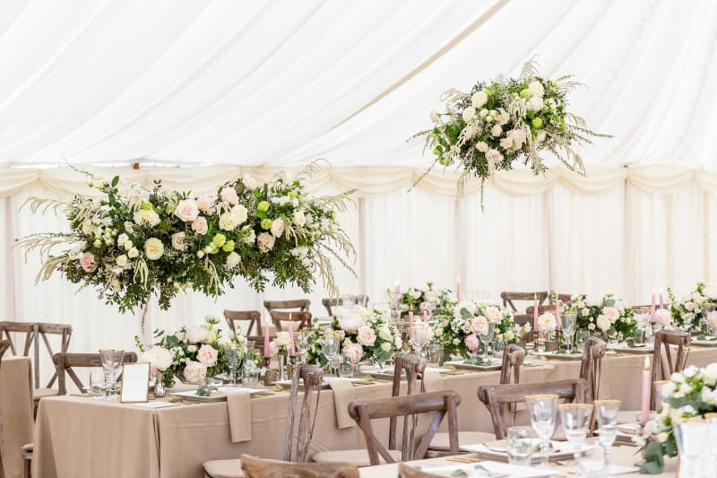 Tables set up and decorated with flowers for a wedding reception under a marquee.