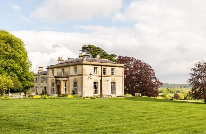 Stately home surrounded by green grass and trees.