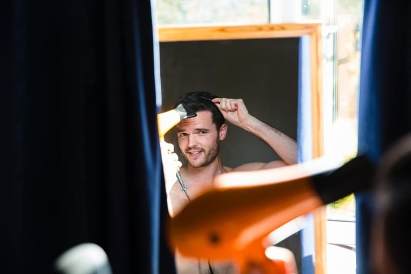 Bridebook.co.uk- groom blow drying his hair in the mirror