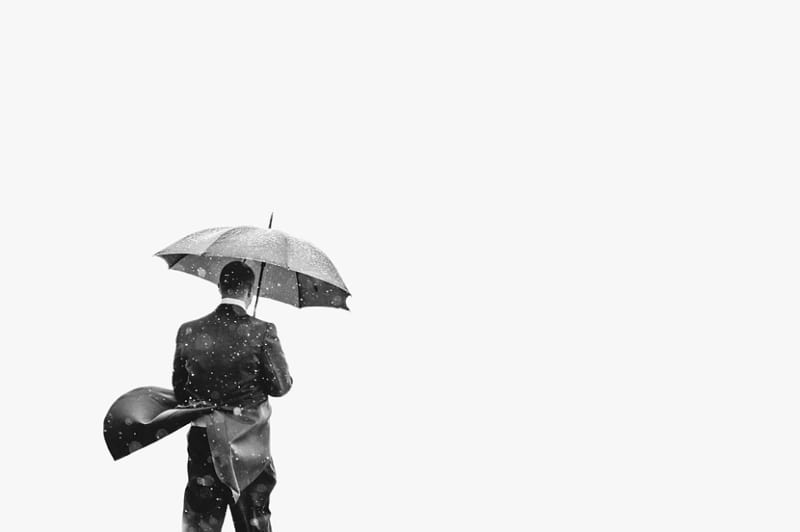 Bridebook.co.uk- groom standing under umbrella in the rain