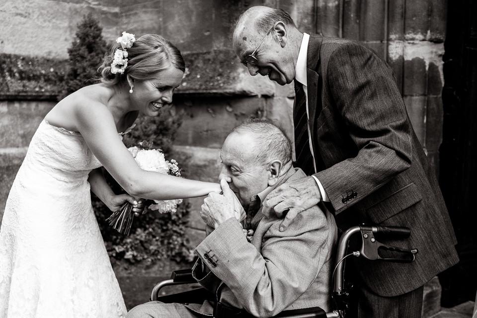 Bridebook.co.uk- bride having her hand kissed by grandfather