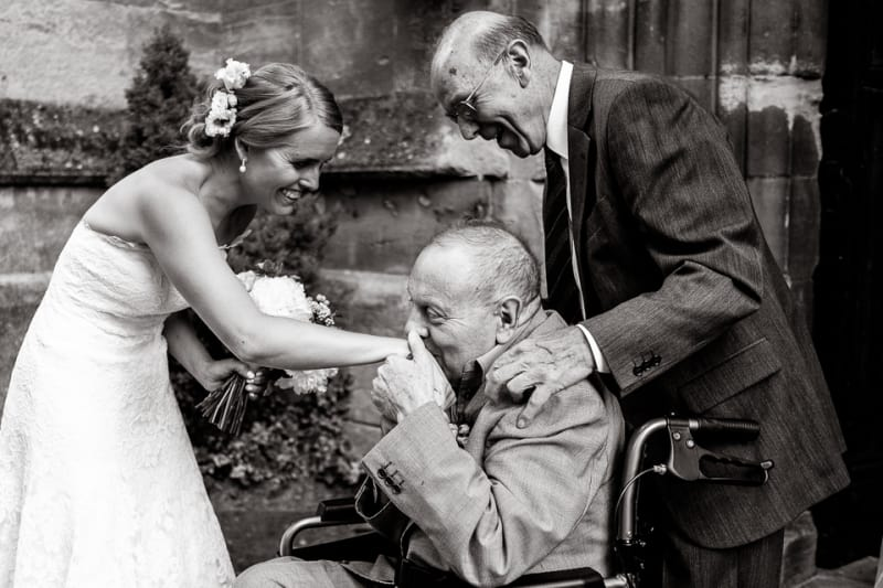 Bridebook.co.uk- bride having her hand kissed by grandfather