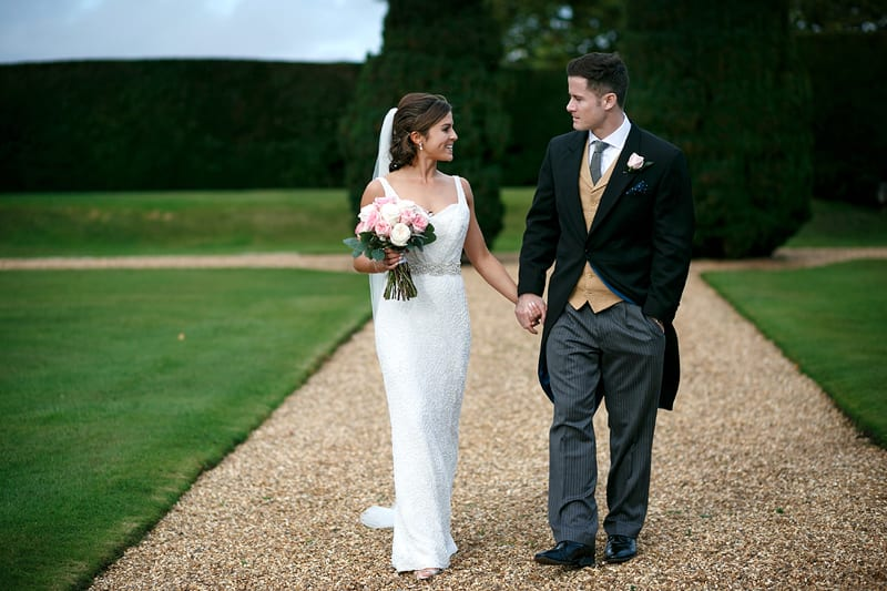 Bridebook.co.uk- bride groom walking in gardens and holding hands