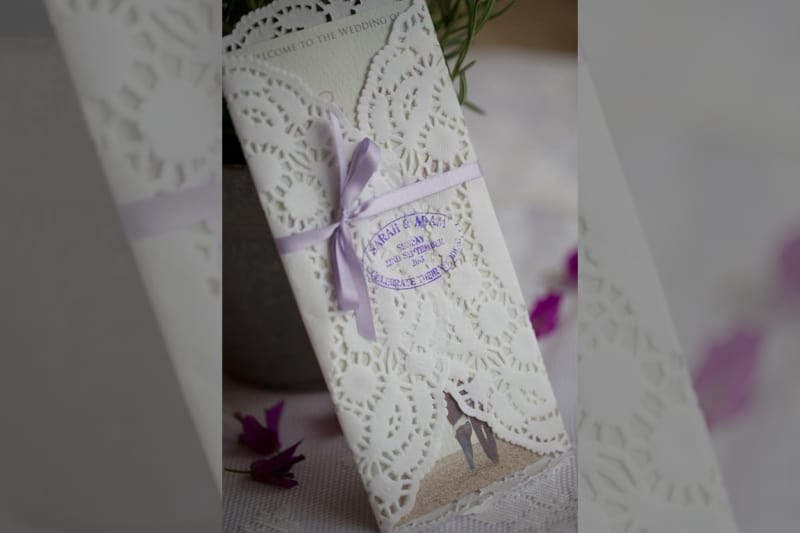 Bridebook.co.uk- laser cut wedding invitation tied with purple ribbon