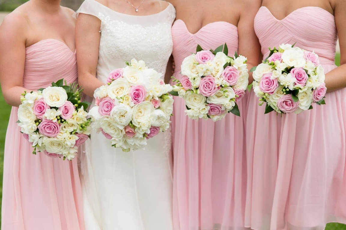 Bridebook.co.uk- bride and bridesmaids holding up white and pink bouquets