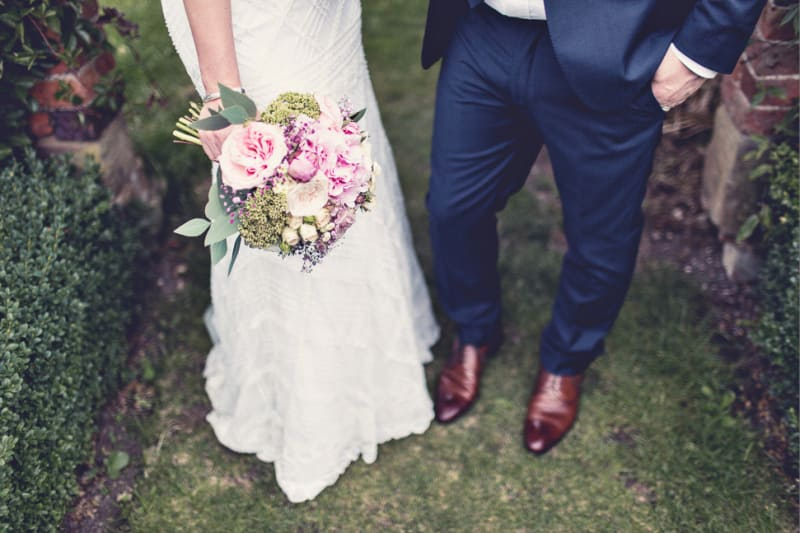 Bridebook.co.uk- bride and groom with bride holding a pink bouquet
