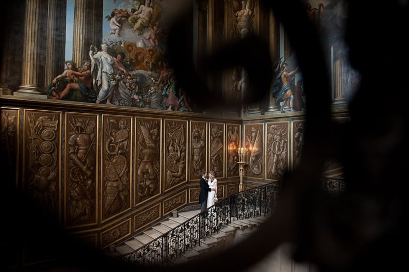 Bridebook.co.uk- groom hugging bride on grand staircase