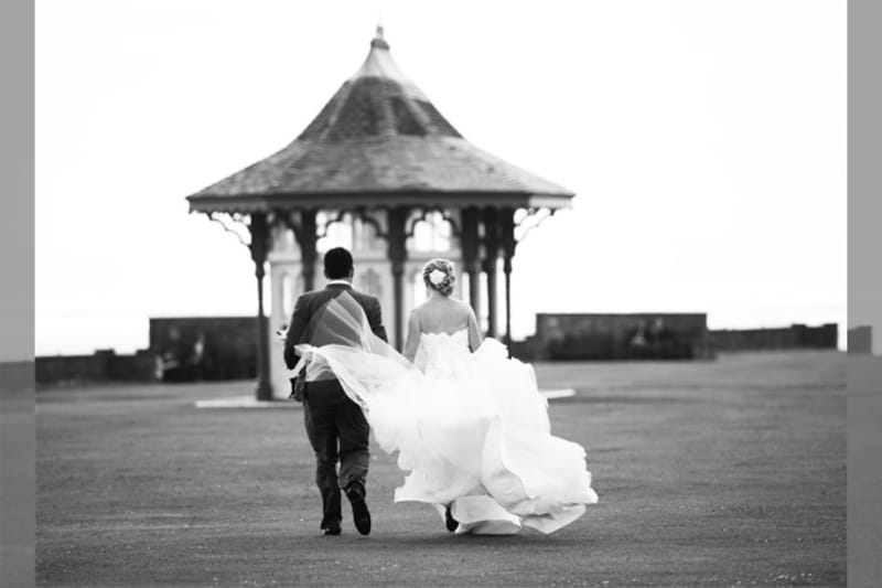 Bridebook.co.uk- and groom walking and bride skirt billowing in the wind