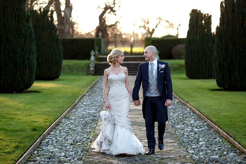 Bridebook.co.uk- bride and groom holding hands and walking