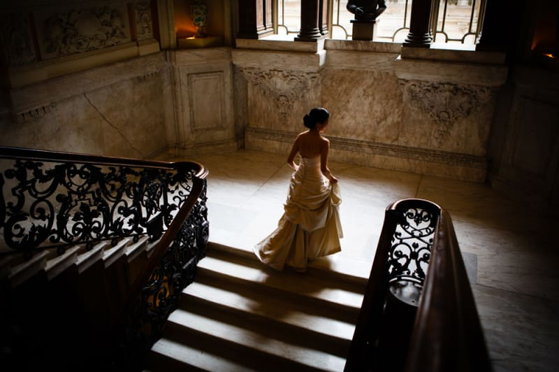 Bridebook.co.uk- bride walking up grand staircase