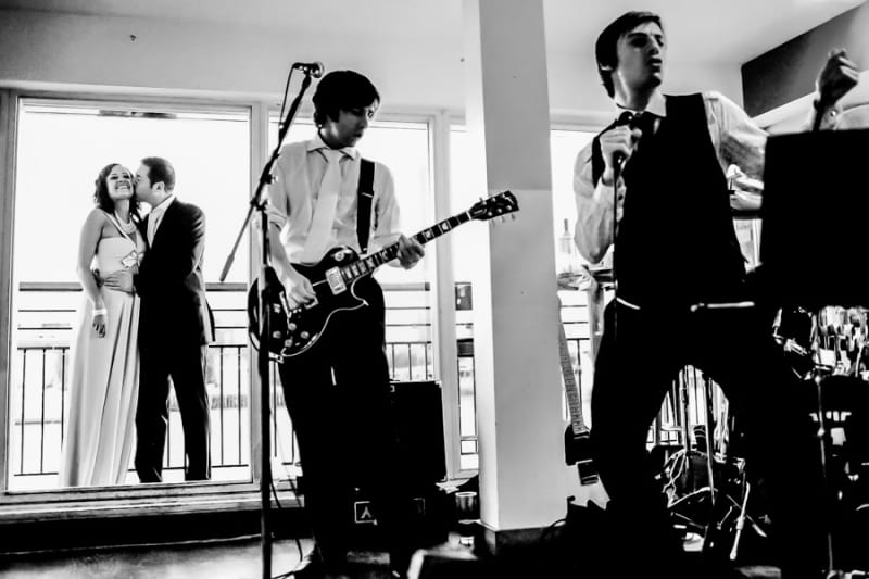 Bridebook.co.uk- wedding band playing as bride and groom watch on